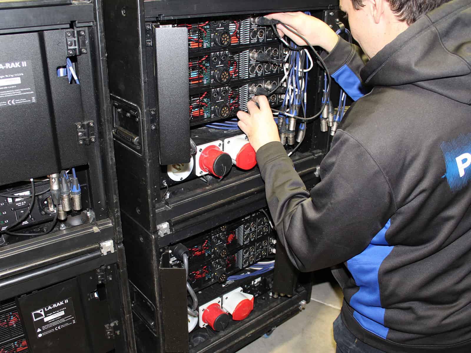 Technician patching amplifier rack